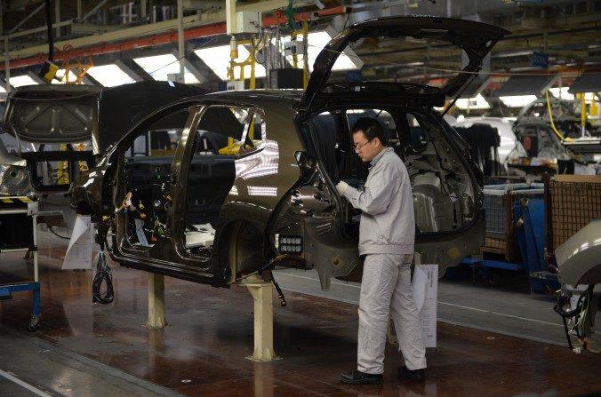 Foto de archivo de trabajadores en la línea de ensamblaje en la planta de la empresa conjunta Sino-French Dongfeng Peugeot-Citroën Automobile (DPCA) en Wuhan, China. China se queda atrás en el desarrollo de motores de automóvil. (Peter Parks/AFP/Getty Images)