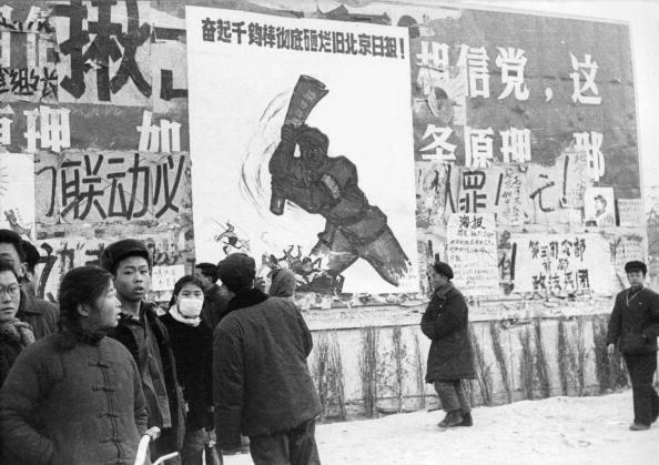 """Un pequeño grupo de jóvenes chinos pasan por varios dazibaos, carteles revolucionarios, en febrero de 1967 en el centro de Beijing, durante la """"Gran Revolución Cultural Proletaria"""". Desde que la revolución cultural se inició en mayo de 1966, el objetivo de Mao era recuperar el poder después de fracaso del """"Gran Salto Adelante"""". (Foto: JEAN VINCENT/AFP/Getty Images)"""