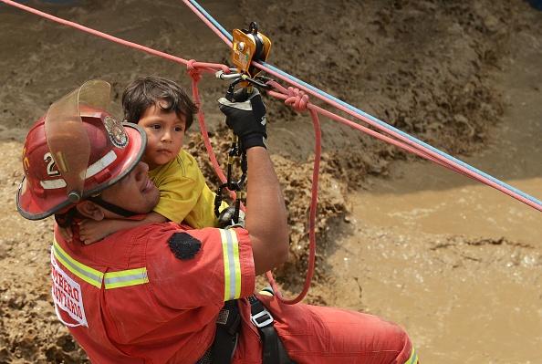Un niño y el bombero son jalados con un arnés de tirolesa. Lima, Perú, el viernes 17 de marzo de 2017. (Foto: CRIS BOURONCLE/AFP/Getty Images)