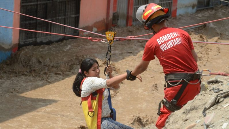 Residente del distrito de Huachipa, al este de Lima, es ayudada el 17 de marzo de 2017 por la policía y los equipos de rescate de bomberos para cruzar las inundaciones repentinas que golpearon su vecindario y aislaron a sus residentes. (CRIS BOURONCLE / AFP / Getty Images)