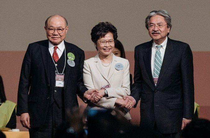 La electa líder ejecutiva de Hong Kong, Carrie Lam (Centro), se encuentra en el escenario con los candidatos para jefe ejecutivo de Hong Kong, John Tsang (derecha), ex secretario financiero de Hong Kong, y Woo Kwok-hing (izquierda), juez retirado, tras el anuncio de las elecciones presidenciales de Hong Kong el 26 de marzo de 2017. (Anthony Kwan / Imágenes Getty)