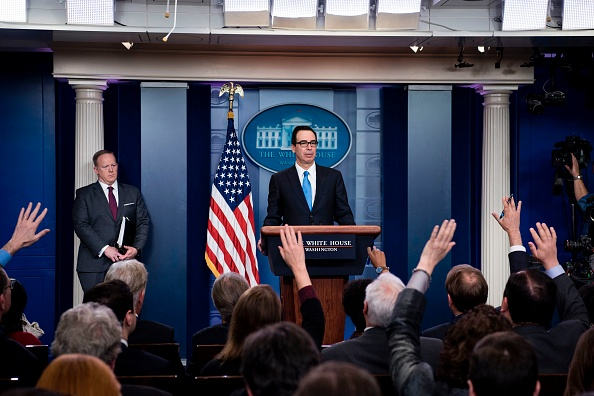 White House Press Secretary Sean Spicer (L) listens while US Secretary of the Treasury Steven Mnuchin speaks during a briefing at the White House April 24, 2017 in Washington, DC. / AFP PHOTO / Brendan Smialowski        (Photo credit should read BRENDAN SMIALOWSKI/AFP/Getty Images)