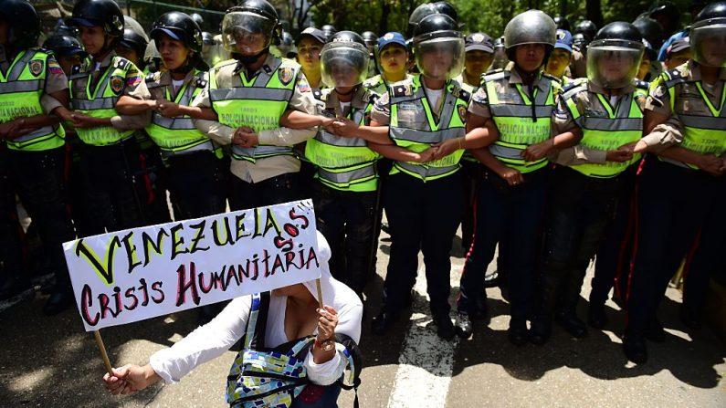 Una manifestante sostiene un cartel que dice 'Venezuela crisis humanitaria SOS', mientras la policía monta guardia en una protesta contra las políticas del gobierno del presidente Nicolas Maduro en Caracas el 26 de mayo de 2016. (RONALDO SCHEMIDT/AFP/Getty Images)