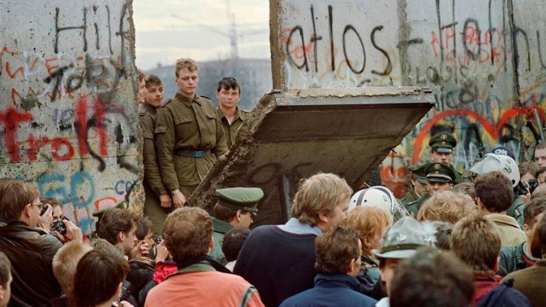 Los berlineses occidentales se agolpan frente al Muro de Berlín a principios del 11 de noviembre de 1989 mientras observan a los guardias fronterizos de Alemania Oriental demoliendo una sección del muro en Berlín, cerca de la Plaza .Potsdamer. (GERARD MALIE/AFP/Getty Images)