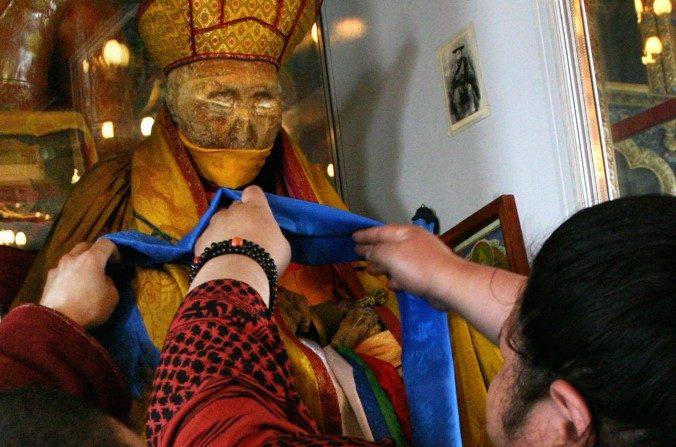 Una foto sin fecha muestra un creyente que decora la momia de Dasha-Dorjo Itighelov, líder budista siberiano que se ve y se palpa igual que cuando murió en 1927 en un templo en Ulan-Ude, la capital de la república de Buriatia. (HO/AFP/Imágenes Getty)