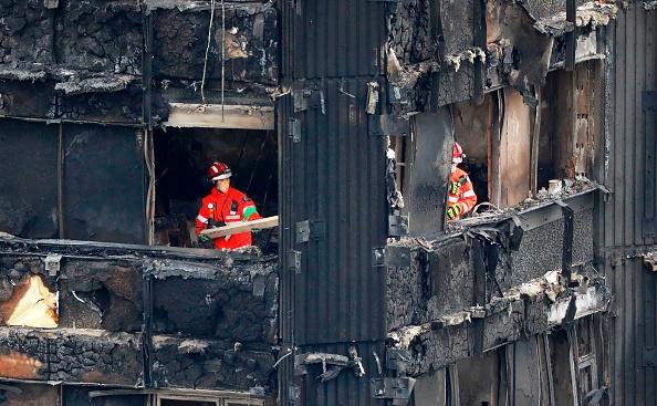 Los miembros de los servicios de emergencia trabajan en los pisos intermedios de los restos calcinados del bloque de la torre Grenfell en Kensington, al oeste de Londres, el 17 de junio de 2017, 3 días después del incendio.  Foto: TOLGA AKMEN/AFP/Getty Images)