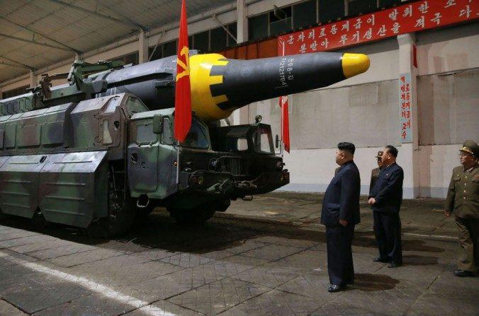 El líder norcoreano Kim Jong Un (izquierda) inspecciona el cohete balístico estratégico Hwasong-12 en una ubicación no revelada en esta fotografía, publicado por medios estatales norcoreanos el 15 de mayo. (STR / AFP / Getty Images)