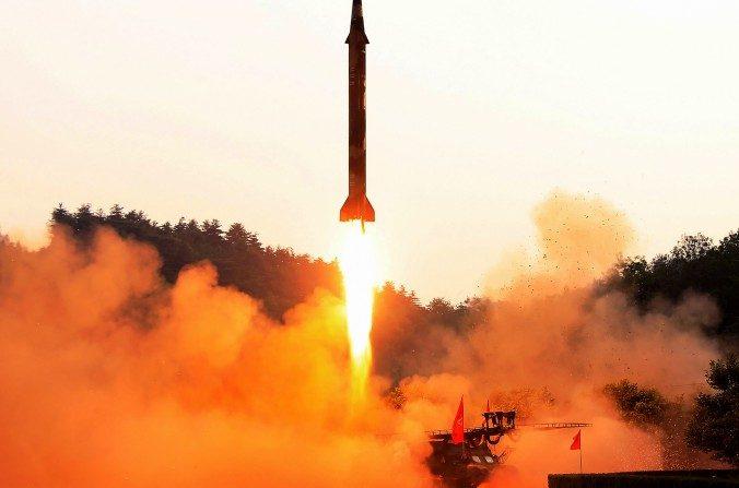 Esta fotografía tomada el 14 de mayo de 2017 y publicada el 15 de mayo, de la agencia central oficial de noticias de Corea del Norte (KCNA), indica que el líder norcoreano Kim Jong-Un (tercero derecha) inspecciona un cohete balístico estratégico de largo alcance de tierra a tierra Hwasong-12 en un lugar no revelado. (STR / AFP / Getty Images)