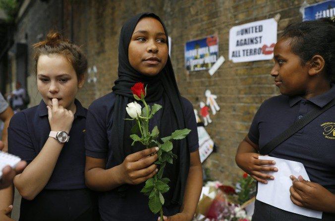 Niños de la escuela primaria Pakeman llegan a poner flores en homenaje a las víctimas del ataque del 19 de junio frente de la mezquita de Finsbury al norte de Londres. (TOLGA AKMEN/AFP/Getty Images)