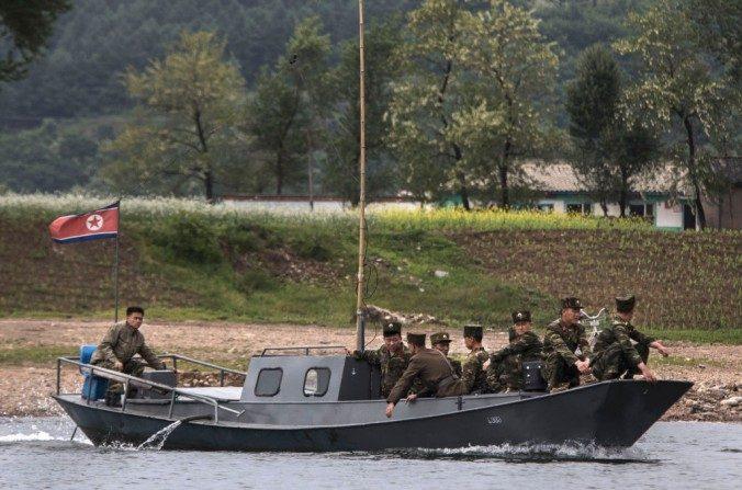 Soldados norcoreanos montan en un barco utilizado como transbordador local mientras que cruzan el río de Yalu al norte de la ciudad fronteriza de Dandong, provincia de Liaoning, en el norte de China cerca de Sinuiju Corea del Norte, El 23 de mayo de 2017. (Kevin Frayer / Getty Images)