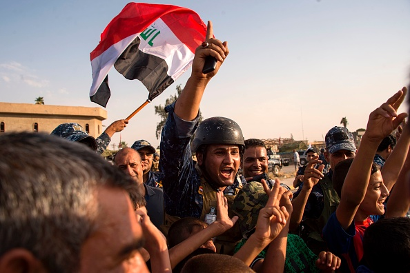 """Los miembros de la policía federal de Irak agitan la bandera nacional de Irak mientras celebran en la Ciudad Vieja de Mosul el 9 de julio de 2017 después del anuncio del gobierno de la """"liberación"""" de la ciudad. Foto: FADEL SENNA/AFP/Getty Images."""