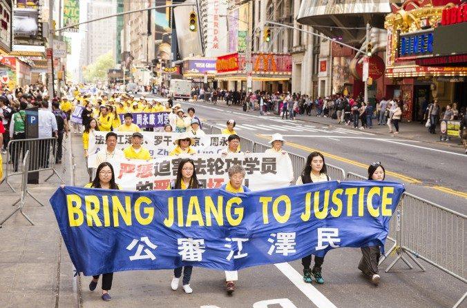 Los practicantes de Falun Dafa sostienen un pendón en referencia a Jiang Zemin, el anterior líder del Partido Chino que es directamente responsable de la persecución a la disciplina Falun Dafa desde julio de 1999. (Edward Dye / La Gran Época)
