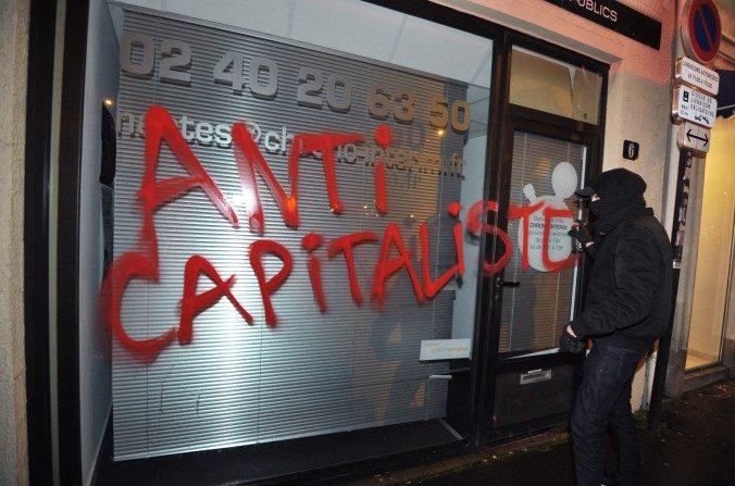 Un miembro del grupo extremista Antifa vandaliza una vidriera en Nantes, Francia, el 14 de febrero de 2014. (FRANK PERRY/AFP/Getty Images)