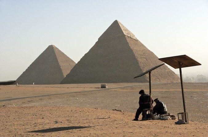 Dos oficiales de policía egipcios vigilan el área de las Grandes Pirámides Chephren y Mycerinus vista al fondo en Giza, El Cairo, Egipto. (Marco Di Lauro/Imágenes Getty)