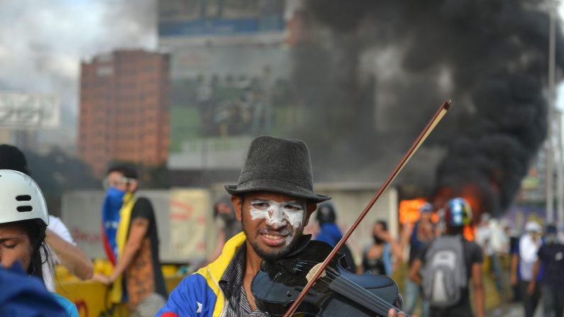 Wuilly Arteaga tocando el violín durante una protesta contra el presidente Nicolás Maduro en Caracas el 27 de mayo de 2017. Ese día fue detenido por la Guardia Nacional Bolivariana y fue liberado el 15 de agosto de 2017. (LUIS ROBAYO / AFP / Getty Images)