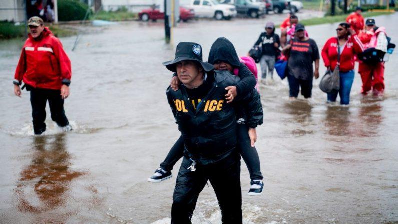 Personas caminan a un bote del sheriff del condado de Harris para escapar de un vecindario inundado durante las secuelas del huracán Harvey el 29 de agosto de 2017 en Houston, Texas. (BRENDAN SMIALOWSKI / AFP / Getty Images)