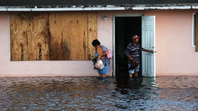 Una pareja deja su hogar inundado la mañana después de que el huracán Irma barrió la zona el 11 de septiembre de 2017 en Bonita Springs, Florida. (Spencer Platt / Getty Images)