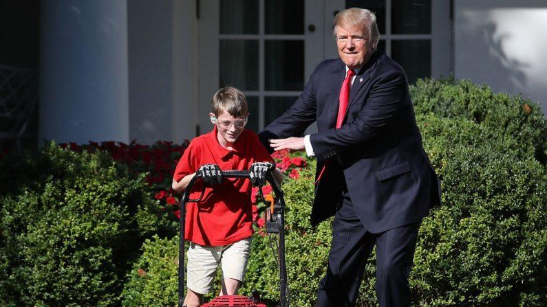 Frank 'FX' Giaccio (Izq.) de 11 años recibe una palmadita en la espalda del presidente estadounidense Donald Trump mientras corta el césped en el Jardín de las Rosas de la Casa Blanca el 15 de septiembre de 2017 en Washington, DC. (Foto de Win McNamee / Getty Images)