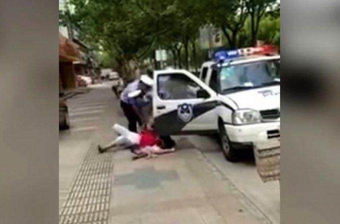 El oficial de policía derribando a la mujer con su hijo en brazos. (YouTube/Captura de pantalla)
