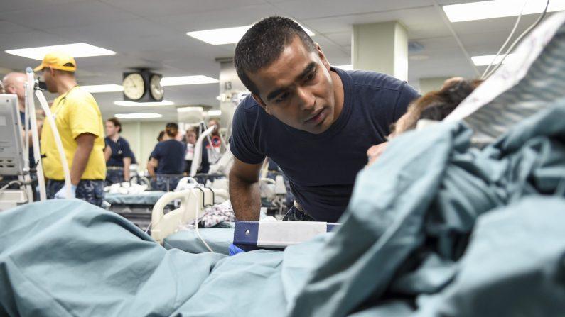 Shiju SantaNivas, enfermero de cuidados intensivos asignado al Centro Médico Militar Nacional Walter Reed, trata a un paciente a bordo del buque hospitalario USNS Comfort, 4 de octubre de 2017. (Foto de U. S. Navy/ Stephane Belcher)