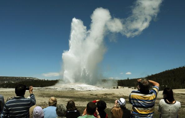 """Turistas observan el géiser """"Old Faithful"""" que estalla en promedio cada 90 minutos en el Parque Nacional de Yellowstone, Wyoming. (MARK RALSTON/AFP/Getty Images)"""
