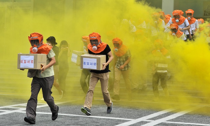Surcoreanos salen corriendo de un edificio durante un simulacro de defensa civil en Seúl el 22 de agosto de 2012. Investigadores del Centro Belfer de Ciencia y Asuntos Internacionales de Harvard publicaron un informe sobre el programa de armas biológicas de Corea del Norte que reclama mejores preparaciones. (JUNG YEON-JE/AFP/GettyImages)