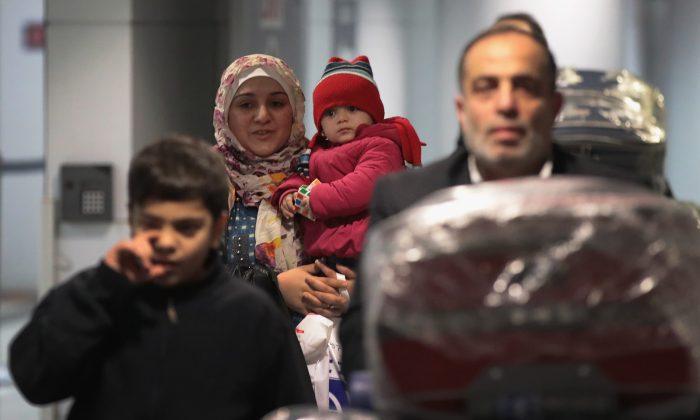 La refugiada siria Baraa Haj Khalaf lleva a su hija Shams mientras pasan por la aduana en el aeropuerto de O' Hare en Chicago en un vuelo desde Estambul, Turquía, el 7 de febrero de 2017. (Escott Olson/Getty Images)