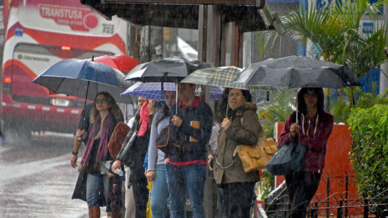 Personas con paraguas esperan en una parada de autobús durante un aguacero causado por la tormenta tropical Nate en Cartago, 25 kilómetros al este de San José, Costa Rica, el 5 de octubre de 2017.(EZEQUIELBECERRA / AFP / Getty Images)