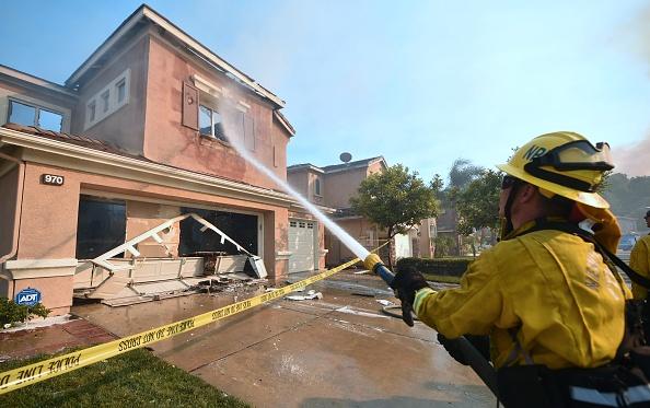 Un bombero apaga un incendio de una casa en un vecindario de Anaheim Hills, en Anaheim, California, el 9 de octubre de 2017. (Fotode FREDERIC J. BROWN / AFP / Getty Images)