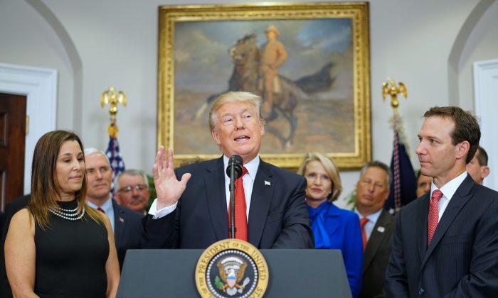 El presidente estadounidense Donald Trump, flanqueado por los empresarios Leslie Baudry (I) y Rich Baudry, habla antes de firmar una orden ejecutiva sobre seguro médico el 12 de octubre de 2017. (MANDEL NGAN/AFP/Getty Images)