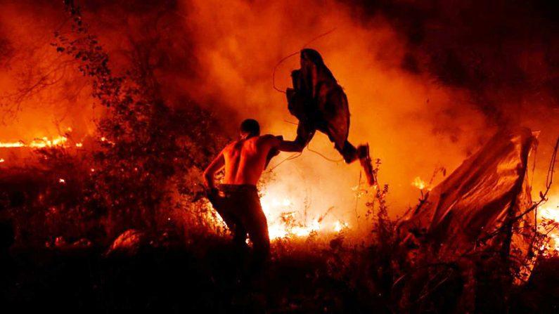 Un hombre intenta enfrentar las llamas en Vigo, noroeste de España, 15 de octubre de 2017. (Foto de  MIGUEL RIOPA / AFP / Getty Images)
