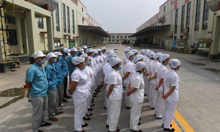 Trabajadores forman fila para cantar canciones comunistas' rojas' en una fábrica de fideos instantáneos, cerca de un pueblo en la provincia central de Henan, China, el 29 de septiembre de 2017. Recientemente, el Partido Comunista Chino extendió aún más su control sobre las empresas de propiedad privada y extranjera, con estructuras del PCCh. (Greg Baker/AFP/Getty Images)