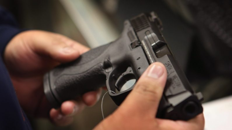 A customer shops for a pistol at a sporting goods store. (Scott Olson/Getty Images)