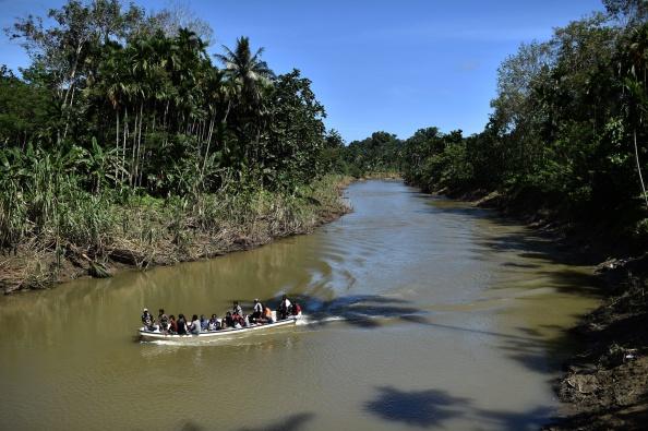 La gente viaja en barco en un río cerca de la aldea de Tora, en la selva de Papua Nueva Guinea, en esta foto de archivo. El explorador británico Benedict Allen debía tomar un vuelo de regreso al Reino Unido desde ese país el domingo 12 de noviembre de 2017. (Aris Messinis/AFP/Getty Images)