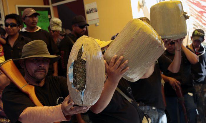Los miembros del grupo Vigilante de la comunidad de Petaquillas muestran armas y marihuana supuestamente incautadas durante una operación para capturar a presuntos delincuentes, en Chilpancingo, Estado de Guerrero, México, el 1 de febrero de 2015. (Pedro PARDO/AFP/Getty Images)