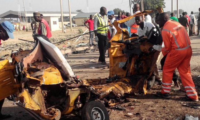 El personal de emergencias está parado cerca de los restos de un vehículo destrozado tras dos atentados suicidas en la ciudad noreste de Maiduguri, Nigeria, el 29 de octubre de 2016. El martes 21 de noviembre, un terrorista suicida mató al menos 50 personas en una mezquita en el noreste de Nigeria. (Joshoua Omirin/AFP/Getty Images)