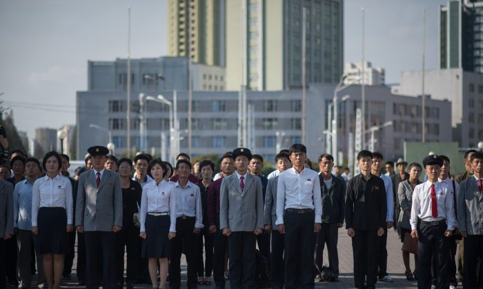 Los norcoreanos observan una declaración formulada por el dictador Kim Jong-un en una pantalla de televisión frente a la estación ferroviaria de Pyongyang el 22 de septiembre de 2017. (ED JONES/AFP/Getty Images)