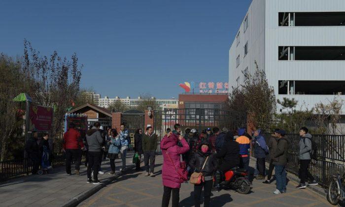 Personas frente a la puerta principal del jardín de infantes RYB Education New World en Beijing el 24 de noviembre de 2017. La policía china ha iniciado una investigación sobre el presunto abuso infantil en la institución de Beijing. (Nicolas Asfouri/AFP/Getty Images)