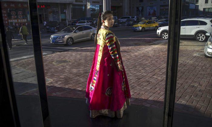 Una trabajadora de un restaurante norcoreano intenta atraer clientes de la ciudad fronteriza de Dandong, provincia de Liaoning, al norte de China, desde la ciudad fronteriza de Sinuiju, Corea del Norte, el 23 de mayo de 2017 en Dandong, China. Los informes desde adentro de China revelan que los trabajadores norcoreanos están siendo forzados a salir del país. (Kevin Frayer/Getty Images)