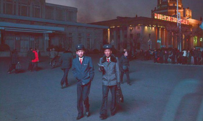 Estudiantes norcoreanos iluminados por una pantalla de televisión pública pasan por la estación central de Pyongyang el 16 de noviembre de 2017. (Ed Jones/AFP/Getty Images)