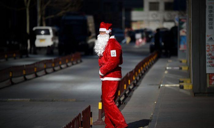 Un vendedor vestido de Papá Noel espera clientes en la entrada de una tienda en Beijing, 25 de diciembre de 2014. (Wang Zhao/AFP/Getty Images)
