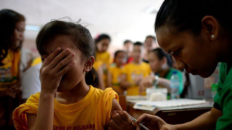 Una estudiante de primaria hace una mueca mientras una enfermera administra una vacuna contra el dengue en la Escuela Primaria Parang en Marikina, al oeste de Manila, Filipinas, el 4 de abril de 2016. (NOEL CELIS / AFP / Getty Images)