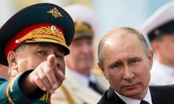 El presidente ruso, Vladimir Putin, habla con el ministro de Defensa, Sergei Shoigu, mientras asisten a la ceremonia del Día de la Armada de Rusia, en San Petersburgo, el 30 de julio de 2017. (ALEXANDER ZEMLIANICHENKO / AFP / Getty Images)