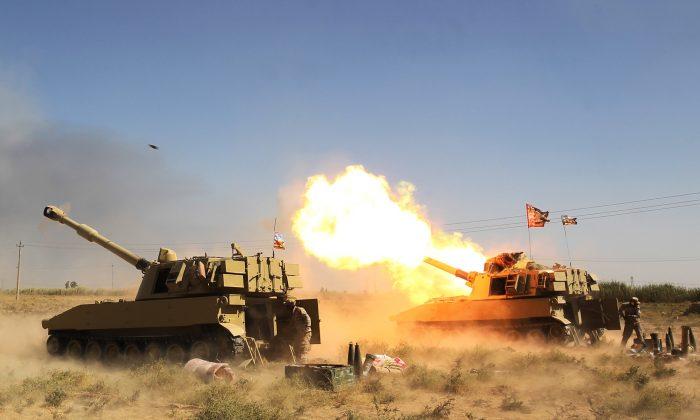 Las fuerzas iraquíes, apoyadas por las unidades de Movilización Popular Hashed al-Shaabi, disparan artillería desde una posición cercana a la fortaleza del grupo ISIS de Hawija, durante una operación para recuperar la ciudad de los yihadistas el 4 de octubre de 2017. (Ahmad Al-Rubaye/AFP/Getty Images)
