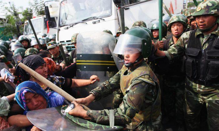 Policías chinos empujan a mujeres uigures que protestan en las calles de Urumqi, capital de Xinjiang, China, el 7 de julio de 2009.(Guang Niu/Getty Images)