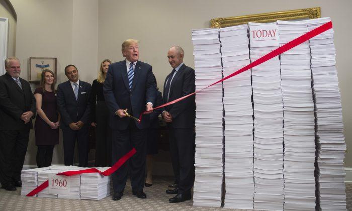 Presidente Donald Trump corta la cinta roja que simboliza  la burocracia entre dos montones de papeles que representan las regulaciones gubernamentales de la década de 1960 y las regulaciones de hoy, el 14 de diciembre. (SAUL LOEB/AFP/Getty Images)