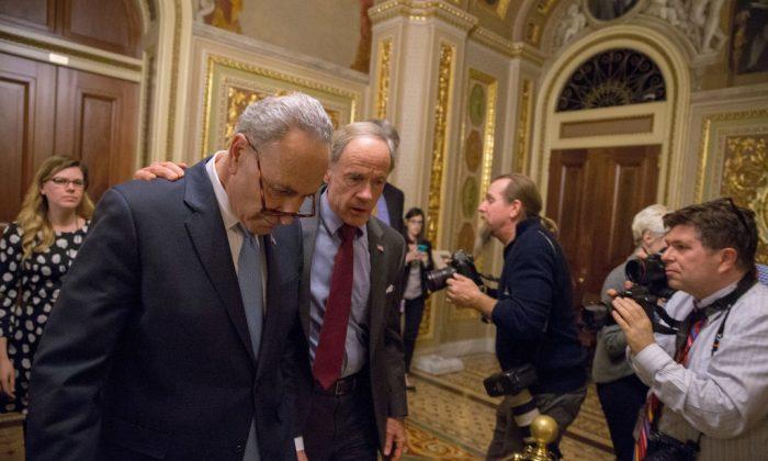 El líder de la minoría del Senado Chuck Schumer (D-NY) y el senador Tom Carper (D-DE) abandonan una reunión demócrata en el Capitolio de los EE. UU. En Washington el 19 de enero de 2018. Una resolución continua para financiar al gobierno ha aprobado la Cámara de Representantes pero falló en el Senado. (Tasos Katopodis / Getty Images)