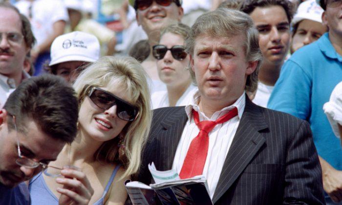 Donald Trump (Der.) y su prometida Marla Maples, disfrutan de la segunda ronda en el torneo abierto de tenis de Estados Unidos, el 28 de agosto de 1991. (Crédito de Timothy A. Clary / AFP / Getty Images)