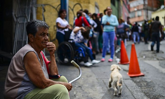Una mujer anciana hace cola para comprar alimentos básicos y artículos domésticos fuera de un supermercado en el barrio pobre de Lidice, en Caracas, Venezuela, el 27 de mayo de 2016. (RONALDO SCHEMIDT/AFP/Getty Images)