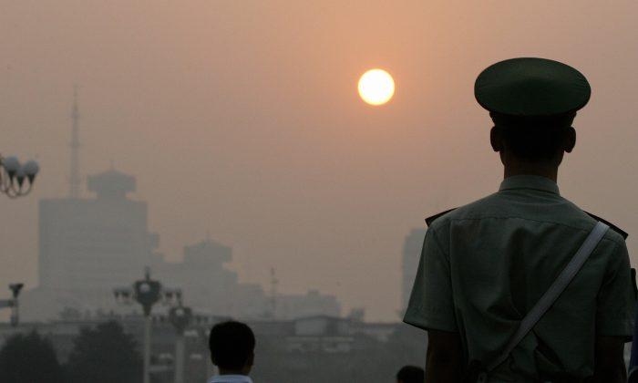Un policía paramilitar mira hacia al amanecer mientras hace la guardia en la plaza de Tiananmen en una nebulosa mañana en Beijing, en esta foto de archivo. (Frederic J. Brown /AFP/Getty Images)